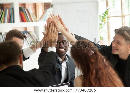 Motivated excited multiracial business team giving high five celebrating corporate growth and financial success, diverse group of colleagues join hands together showing unity help support in teamwork #793409206
