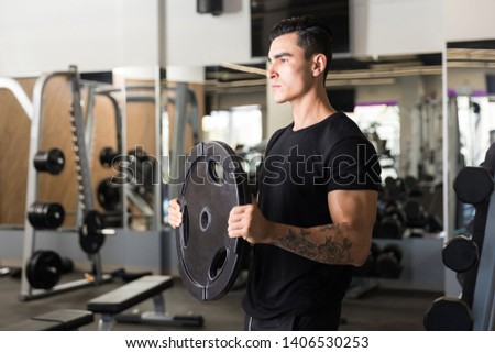 Motivated gym instructor lifting weight disc while standing at health club