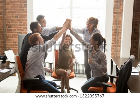 Motivated happy diverse business office people employees group give high five with coach mentor engaged in team win result promise support integrity in teamwork, celebrate cooperation reward concept