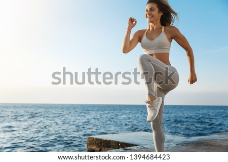 Motivated happy sporty woman wearing sports bra, sneakers enjoying excercise, training outdoors near sea, workout quay, jogging, running, jumping energized, smiling during productive fitness session Foto stock ©