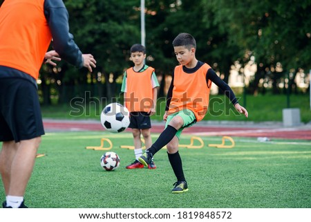 Motivated kid player in football uniform working out the kicking ball together with his experienced coach on sport field