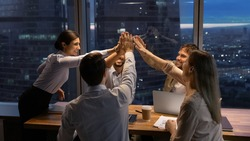 Motivated multinational team raise high fives on briefing after finding problem solution as successful brainstorm result. Happy workers unite hands above conference desk celebrate common achievement