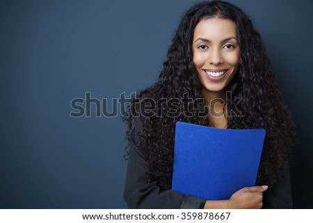 Motivated young African American job seeker clutching a blue CV in her hands standing against a blue background with copy space beaming at the camera