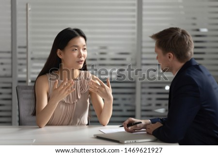 Motivated young Asian female work candidate talk share thoughts with male employer or recruiter, serious millennial biracial woman applicant speak with hr manager at job interview in office