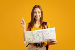 Motivated young woman tourist holding city map, yellow studio background. Happy lady with backpack holding map, looking for new destinations to travel, showing eureka gesture, copy space