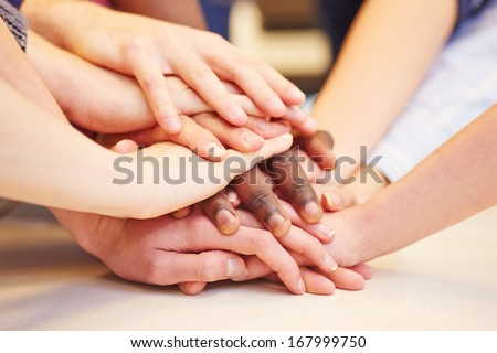 Motivation and teamwork with many hands stacked in school