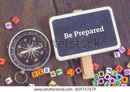 Motivation concept image,word BE PREPARED over top view flat lay wooden signage and compass on wooden background.selective focus shot #604717679