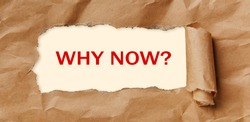 Motivation encouragement quote. Text - WHY NOW - appearing behind torn brown paper.