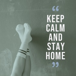 Motivation quote on woman legs relaxing on wall keep calm and stay home about self quarantine and social distancing concept during the spread of Covid-19 and coronavirus