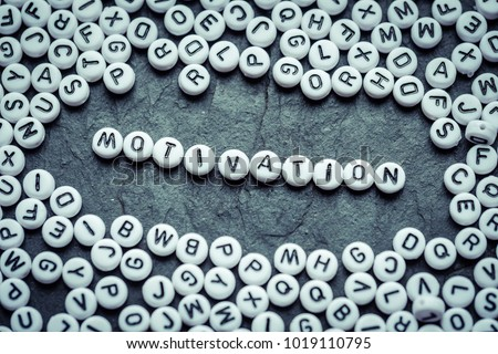 Motivation words MOTIVATION made from small white letters on black stone background