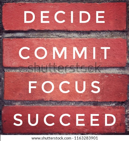 Motivational and inspirational quote - 'DECIDE, COMMIT, FOCUS, SUCCEED' written on red brick wall. Vintage styled background.