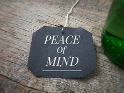 Motivational and inspirational quote - 'Peace of mind' written on a black piece of paper. Vintage styled background.