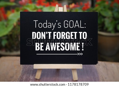 Motivational and inspirational quote - 'Today's goal: DON'T FORGET TO BE AWESOME!' on a blackboard. Blurred vintage styled background.
