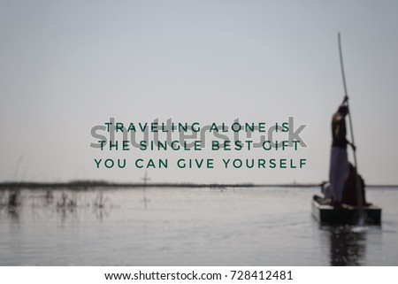 Motivational and inspirational quotes - Traveling alone is the single best gift you can give yourself. With blurred styled background of a lake and sky. #728412481