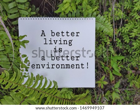 motivational and inspirational words of a better living is a better environment on notepad with green leaves background #1469949107