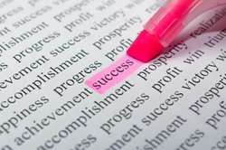Motivational concept: person highlight the word success between many other words with a pink highlighter