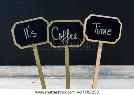 Motivational message Its Coffee Time written with chalk on wooden mini blackboard labels, defocused chalkboard and wood table in background #497788258