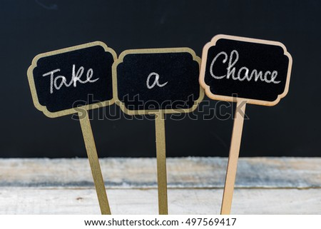 Motivational message Take A Chance written with chalk on wooden mini blackboard labels, defocused chalkboard and wood table in background #497569417