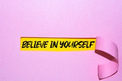 Motivational quote. Believe in yourself written on white card with paper clip.