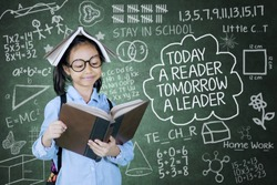 Motivational quote concept, cute girl reading a textbook and a book over her head while standing with scribbles on the chalkboard