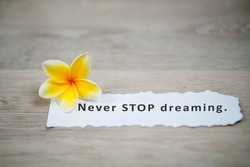 Motivational quote - Never STOP dreaming. Positive  note message on a white notepaper with yellow Bali plumeria flower on white wooden board background.