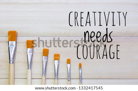 Motivational quotes or inspirational quotes - CREATIVITY NEEDS COURAGE with wooden background and paint brush . #1332417545