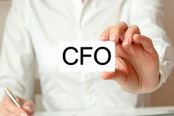 Motivational words: CFO. A woman in a white shirt holds a piece of paper with the text: CFO. Business concept for companies. CFO - short for Chief Financial Officer.