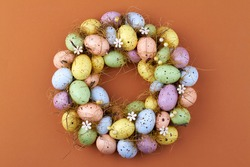 Motley easter eggs on brown background.