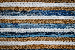 motley striped Patchwork rug from denim jeans fabric. Recycle old jean denim floor mat, door mat, area rug. Recycling cloth carpet. Zero waste concept. Boho style background. Cozy home.