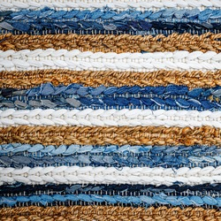 motley striped Patchwork rug from denim jeans fabric, top view. Recycle old jean denim floor mat, door mat, area rug. Recycling cloth carpet. Zero waste concept. Boho style background. Cozy home.
