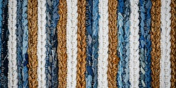 motley striped rug from denim jeans fabric, top view. Recycle old jean denim floor, door mat, area rug. Recycling cloth carpet. Zero waste concept. Boho style background. Cozy home. Banner.