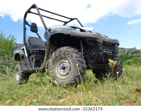 Moto all-terrain vehicle in mountains against blue sky