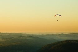 Moto paraglider above the landscape in sunset, copy space