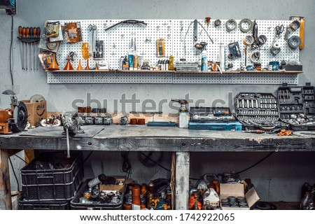 Moto workshop with hand tools. Workbench with sets of keys, screwdrivers, ploskobets, electrical tape, duct tape on the wall. Table with motorcycle parts, vise. Workspace for a joiner, auto mechanic Foto stock ©