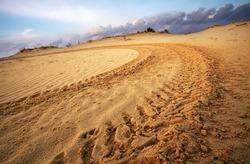Motocross and auto sport track on blue sky background. Wheel tracks on sand