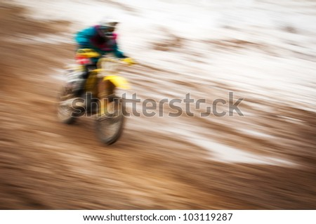 Motocross bike rider in motion with snow on background