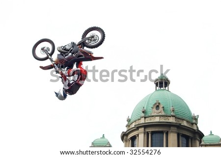 Motocross biker performing dangerous trick - back flip next to cupola of old stylish building isolated on white