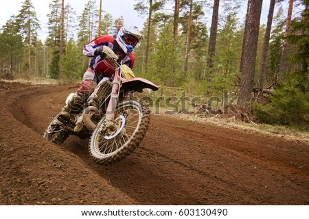 Motocross driver in action accelerating the motorbike after the corner on the race track. #603130490