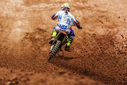 Motocross, enduro rider accelerating in dirt track with debris flying away