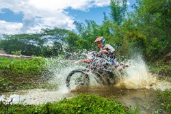 motocross,enduro rides through the mud with big splash,driver splashing mud on wet and muddy terrain,Motocross racer in a wet and muddy terrain covering the driver completely.