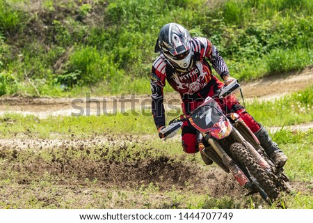 Motocross. Motorcyclist in a bend rushes along a dirt road, dirt flies from under the wheels. Close-up. Active extreme rest. #1444707749
