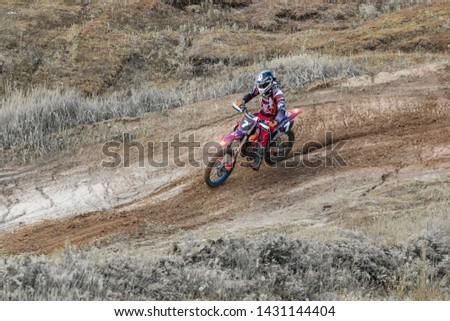 Motocross. Motorcyclist rushes along a dirt road, dirt flies from under the wheels.  Active extreme rest. #1431144404