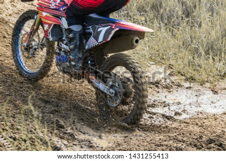 Motocross. Motorcyclist rushes along a dirt road, dirt flies from under the wheels.  Active extreme rest. #1431255413