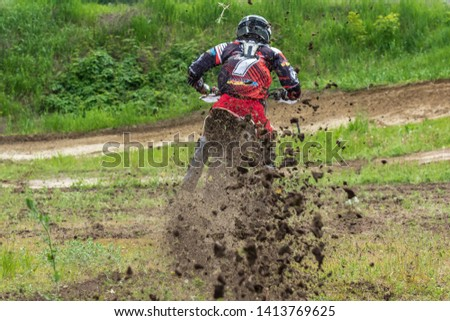 Motocross. Motorcyclist rushes along a dirt road, dirt flies from under the wheels. Against the backdrop of bright spring greens. Close-up. Active extreme rest. #1413769625