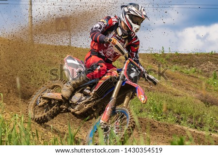 Motocross. Motorcyclist rushes along a dirt road, dirt flies from under the wheels.  Close-up. Active extreme rest. #1430354519