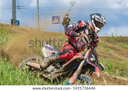 Motocross. Motorcyclist rushes along a dirt road, dirt flies from under the wheels. Green vegetation and blue sky.  Close-up. Active extreme rest. #1431736646