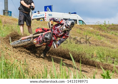 Motocross. Motorcyclist rushes along a dirt road, dirt flies from under the wheels. Photographers near. Doctors are watching. Close-up. Active extreme rest. #1413198971