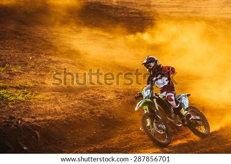 Motocross pilot in a turn during sunset with golden smoke on dirt track