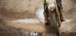 Motocross racer in a wet and muddy terrain. Water and mud splashing everywhere and covering the driver