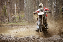 Motocross racer on wet and muddy terrain in Finland